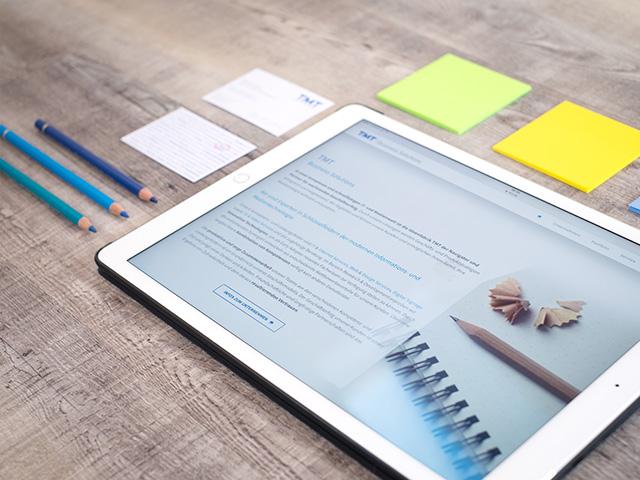 Schreibtsich aus Holz mit Notizbuch, Laptop Macbook iPhone und Tasse