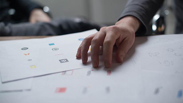 Viele Logos auf Papier, liegen auf Schreibtisch, Hand darauf, Mensch unscharf im Hintergrund
