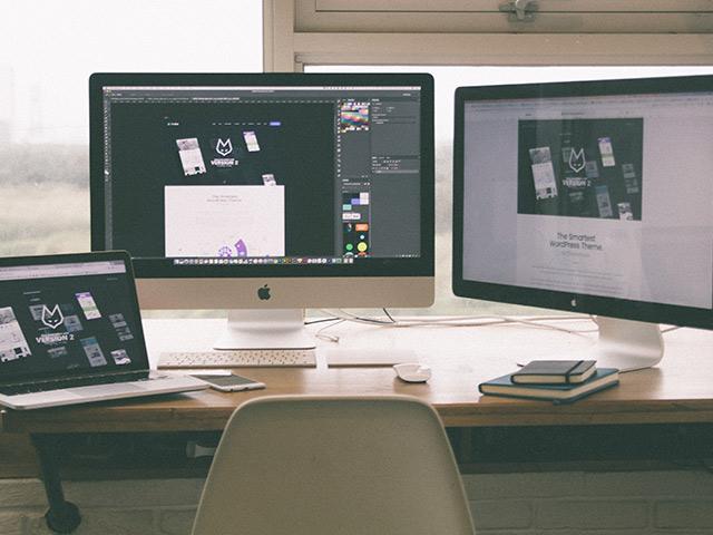 Schreibtisch vor Fenster mit Macbook, iMac und Monitor