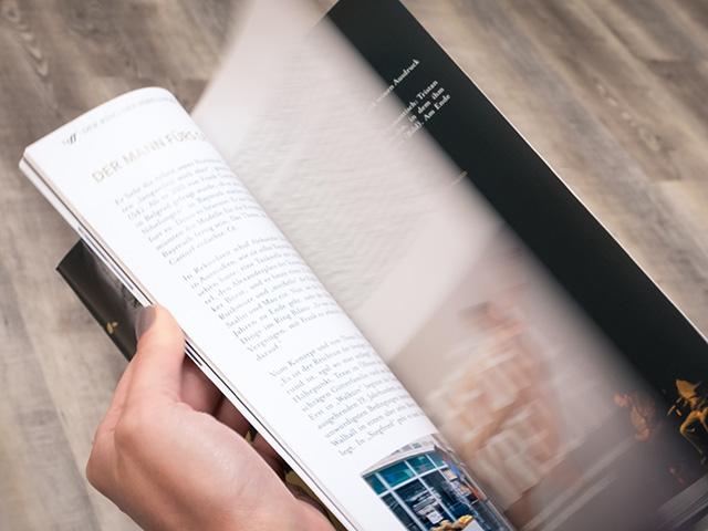 Frau im Anschnitt blättert durch einen Katalog