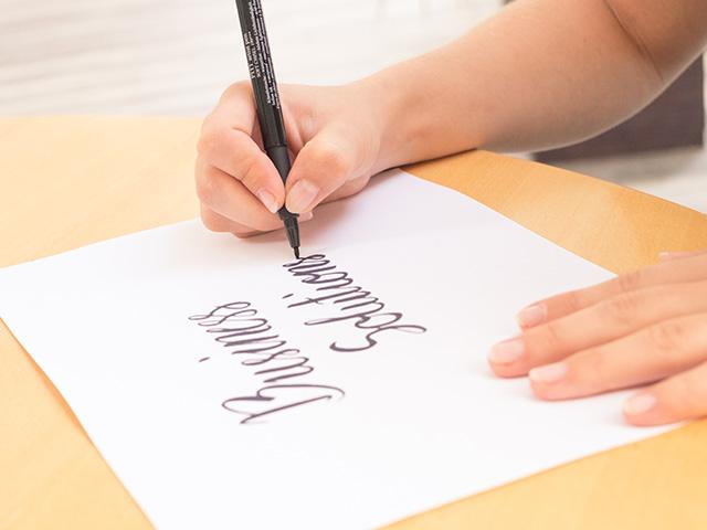 Holztisch mit Laptop Mann mit Hand auf Tastatur und andere Hand zeichnet ein Logo auf Papier