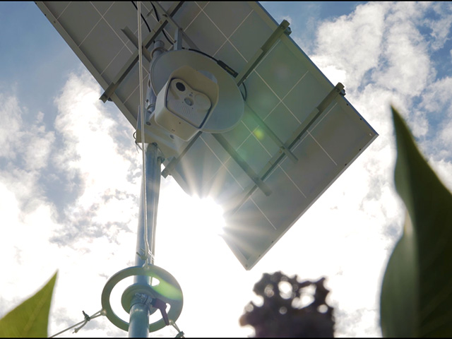 IT Service Webcam mit Solarpanel unter blauem Himmel